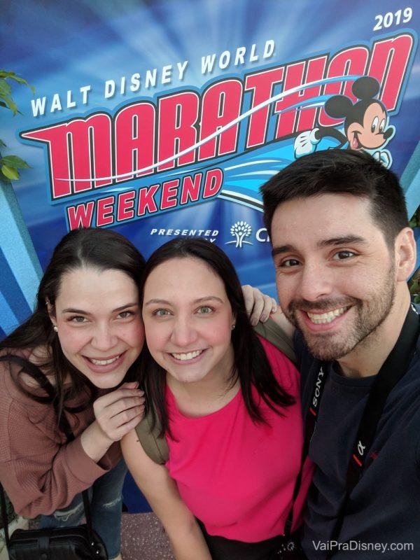 Foto da Bia, Renata e Felipe sorrindo em frente ao cartaz da maratona da Disney