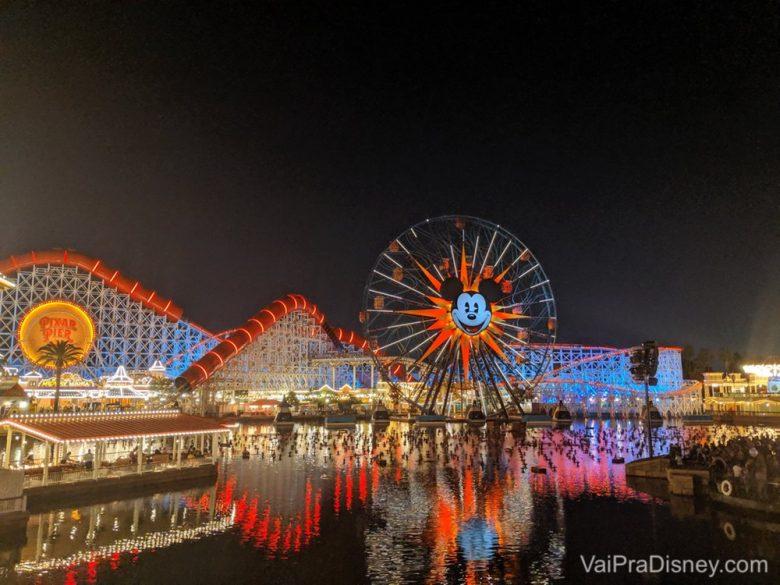 Foto da roda gigante com o Mickey no centro e do Pixar Pier todo iluminado à noite na Disneyland California