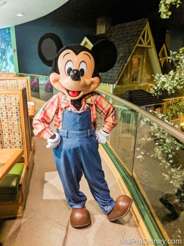 Foto do Mickey fazendeiro que aparece no jantar do Garden Grill, uma das refeições com personagens do complexo Disney. Ele está usando jardineira jeans, camisa xadrez e botas.