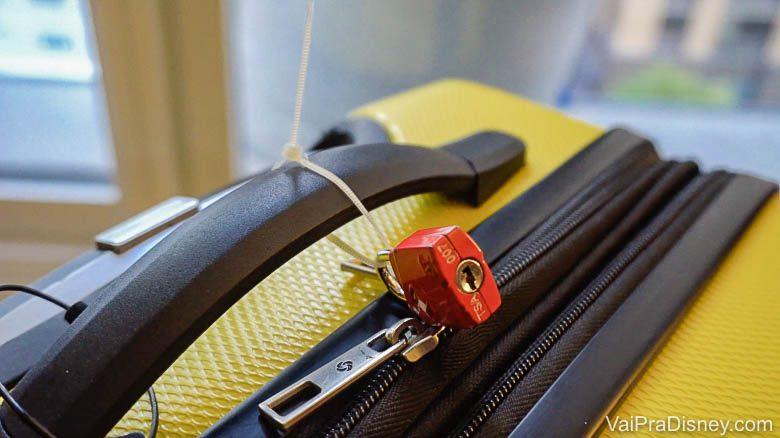 Foto de uma mala amarela com um cadeado no zíper, um recurso para evitar roubos e furtos de bagagem na viagem