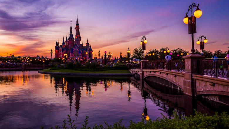 Foto do castelo da Cinderela à noite, com o parque ao redor iluminado. Os parques da Disney fecharam no mundo todo devido à pandemia do coronavírus