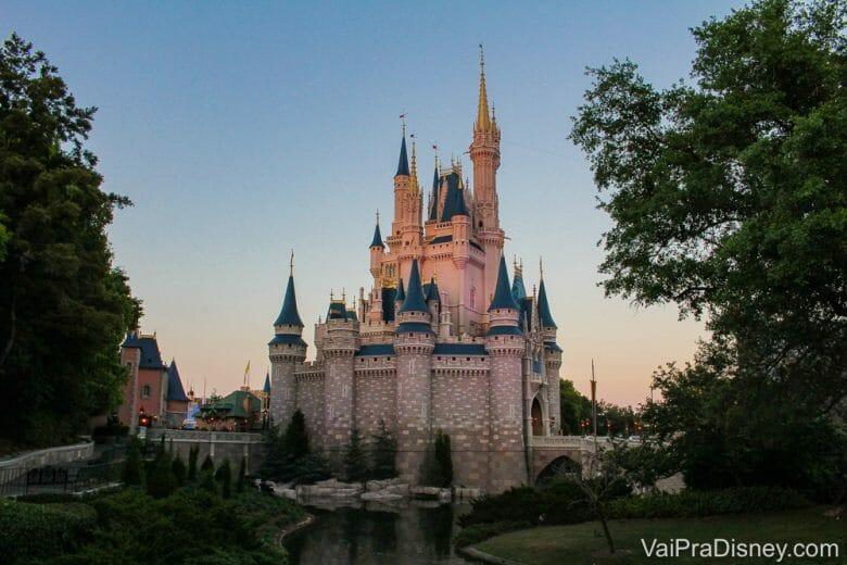 Foto do castelo da Cinderela no Magic Kingdom com o céu escurecendo atrás, em tons de azul e rosa