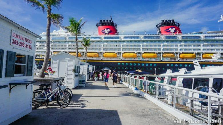 Imagem do navio de cruzeiro da Disney parado no porto, com visitantes em volta e o céu azul atrás