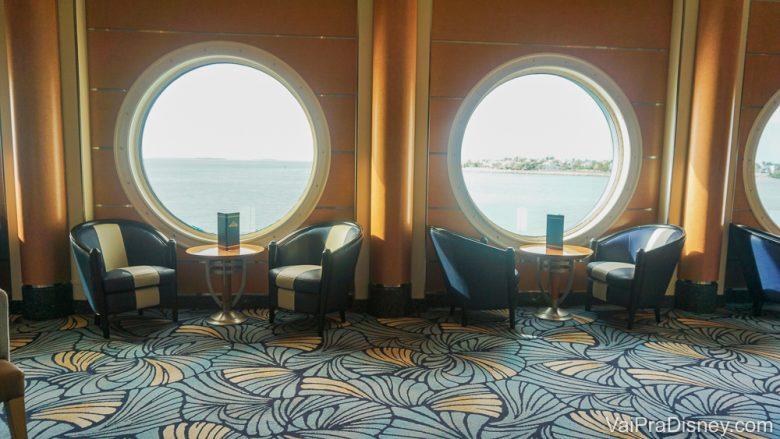 Foto da área comum do cruzeiro da Disney, com mesas e poltronas e janelas redondas.