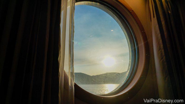 Foto da janela da cabine do cruzeiro da Disney, redonda, com o mar visível através dela.