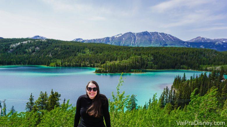 Foto da Bia no cruzeiro que ela fez sozinha, com a paisagem do Alaska ao fundo. Há um lago, montanhas e vegetação.