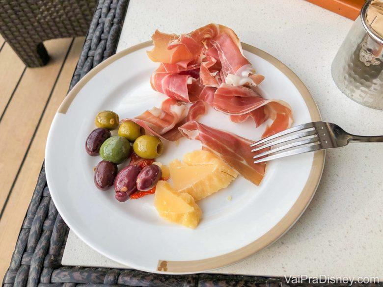 Foto de um prato com petiscos no cruzeiro, com azeitonas, queijos e presunto de parma.