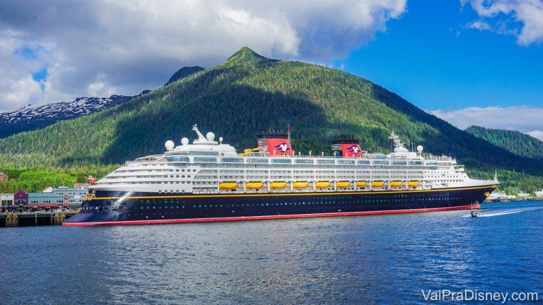 Foto do navio de cruzeiro da Disney em alto mar, com montanhas ao fundo. Os cruzeiros também precisaram se adaptar para evitar a transmissão do coronavírus