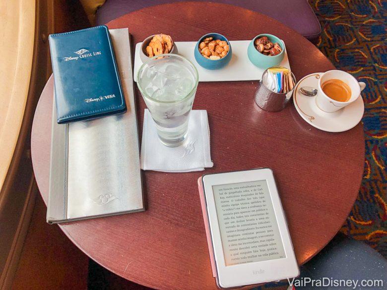 Foto da mesa da Bia no cruzeiro, com café, água, um cardápio, petiscos e um kindle.
