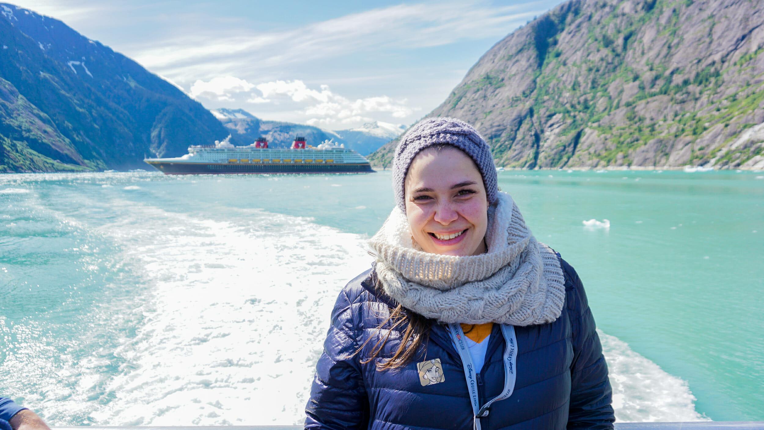 Foto da Bia com a paisagem do Alaska ao fundo. É possível ver o mar, uma montanha e o navio do cruzeiro da Disney