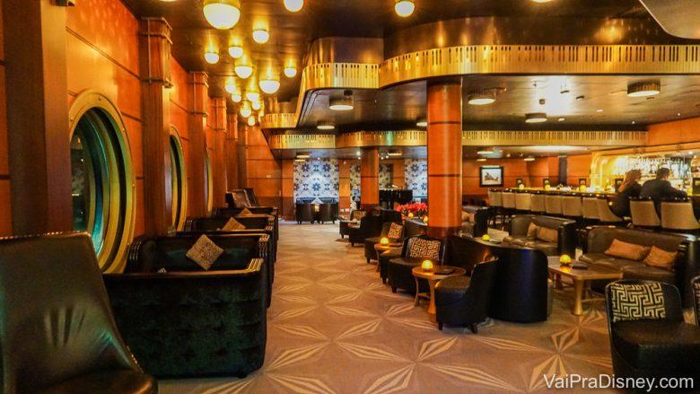 Foto do bar só para adultos no Disney Magic, com poltronas de couro e painéis de madeira na parede.