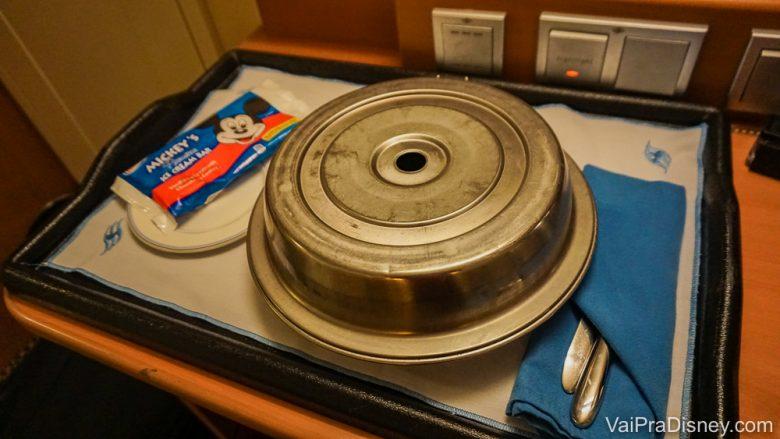 Foto da bandeja do room service do cruzeiro, com um prato coberto, talheres e um sorvete do Mickey ao lado