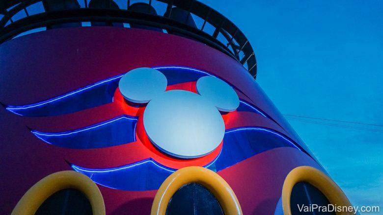 Foto do Mickey que decora parte do navio da frota da Disney Cruise Line. O símbolo é branco e o fundo é listrado em vermelho e azul.