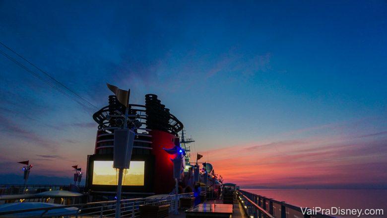 Foto do pôr do sol no navio da Disney, com o céu em tons de azul e rosa. A Bia fez essa viagem sozinha e aproveitou muito!