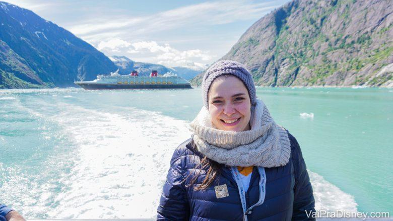 Foto da Bia no cruzeiro que ela fez sozinha, com a paisagem do Alaska ao fundo. É possível ver o mar, uma montanha e o navio do cruzeiro da Disney