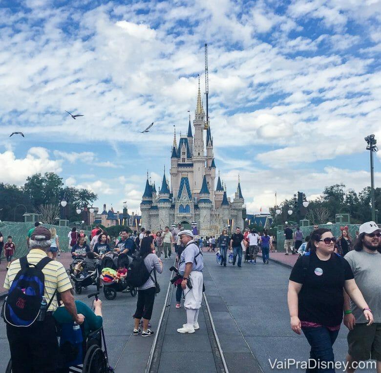 Foto do castelo da Cinderela no Magic Kingdom, com visitantes passando em frente e o céu azul ao fundo.