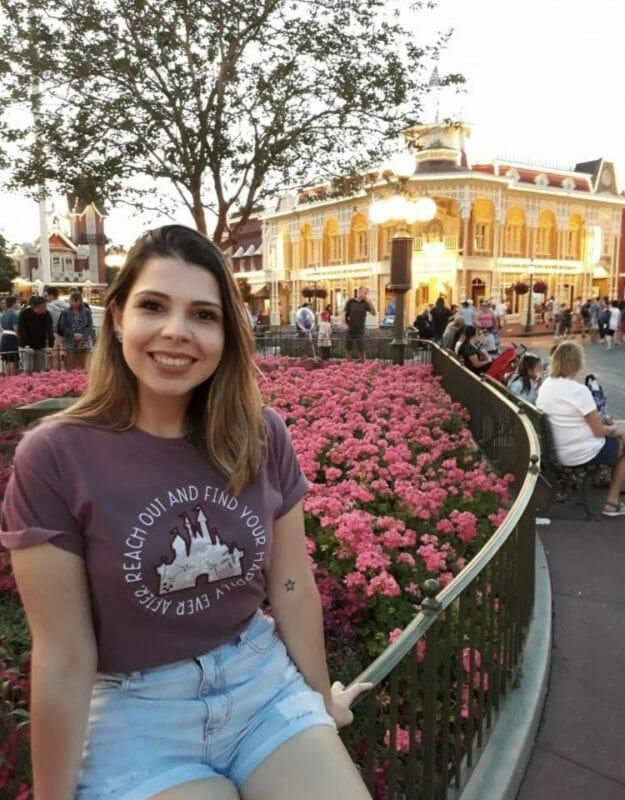 Foto da Helen sentada na grade da Main Street, com flores cor-de-rosa atrás