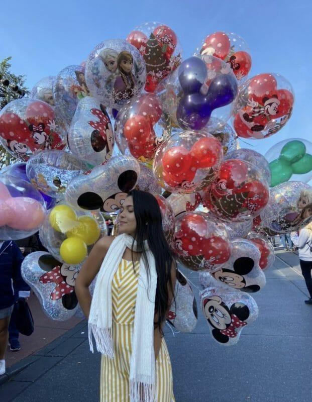 Foto da Inaê rodeada pelos balões que ficam à venda na Main Street