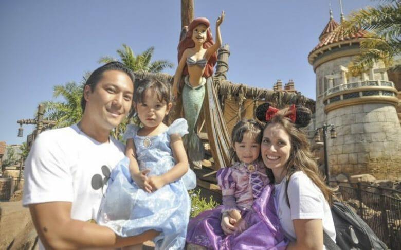 Foto da família de leitores do VPD posando com a Ariel em frente à atração na Fantasyland
