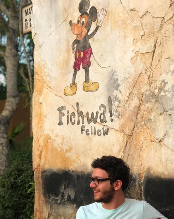 Foto do Marcelo, da equipe do VPD, em uma parede que tem o Mickey no Animal Kingdom
