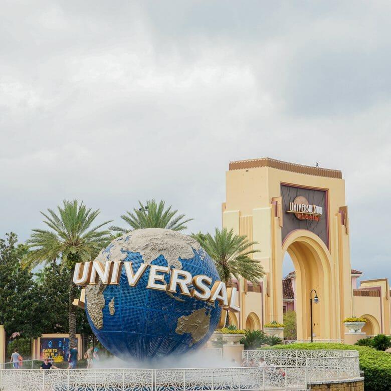 A imagem mostra a entrada do Universal Studios, que mostra o globo, símbolo da Universal, com o nome escrito em letras grandes ao seu redor.