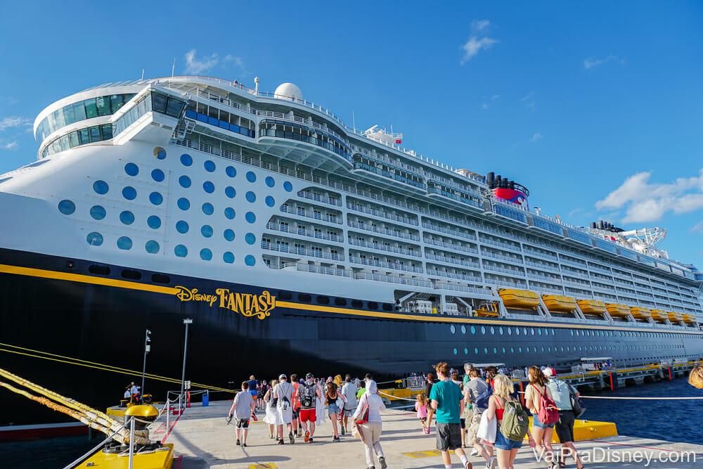 Imagem do navio de cruzeiro da Disney parado no porto, com visitantes em volta e o céu azul atrás. O navio é o Disney Fantasy, segundo as letras em amarelo escritas sobre ele.