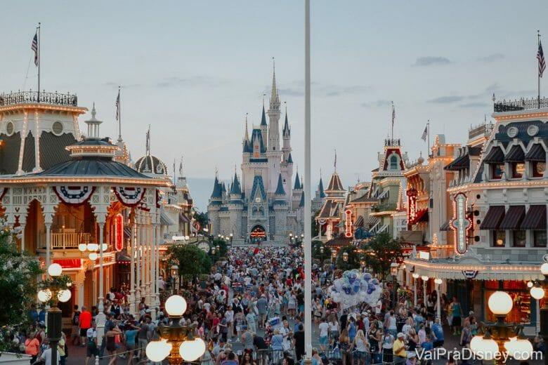 Foto do Magic Kingdom em um dia bem cheio, com visitantes passando pela Main Street que já tem algumas luzes acesas