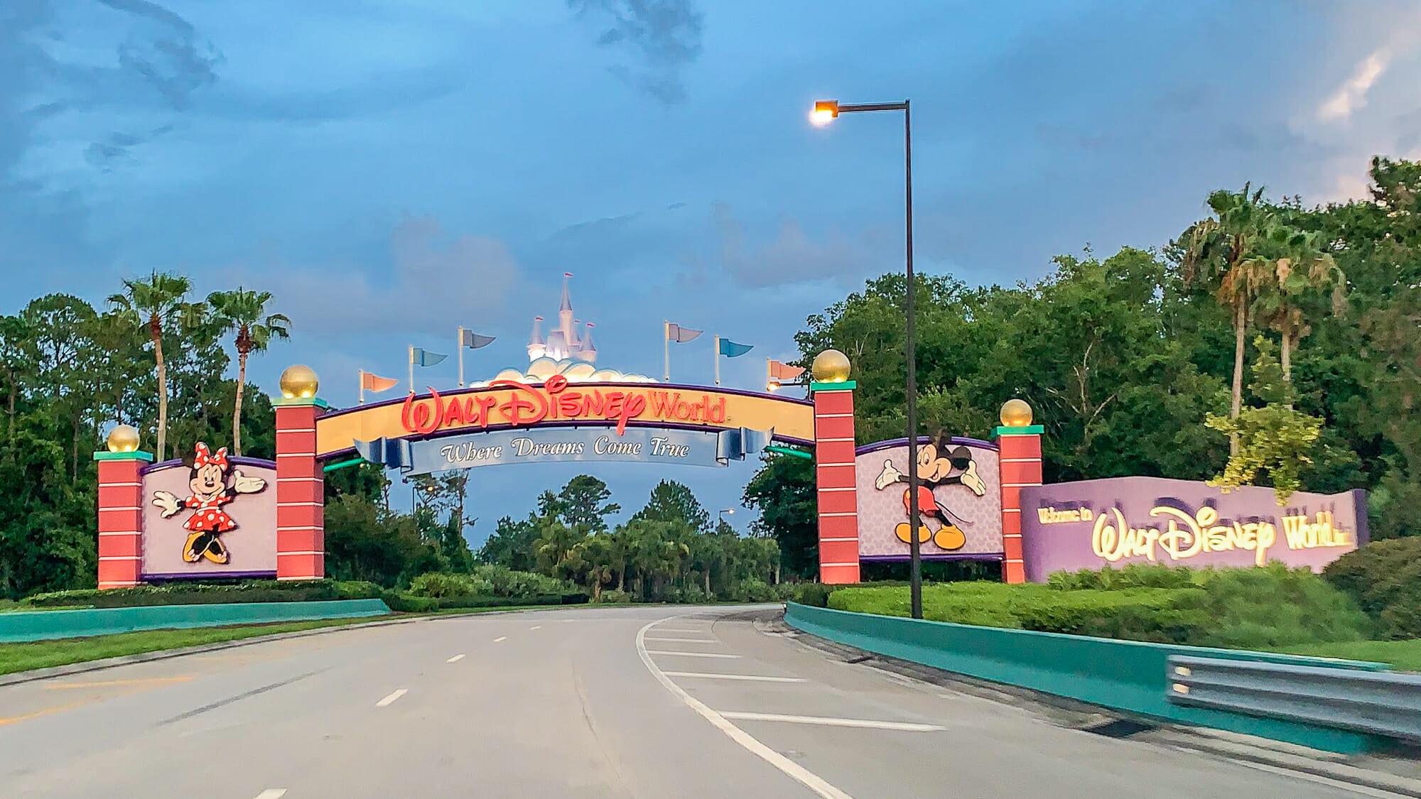 Foto do portal de entrada do complexo da Disney, que tem a Minnie e o Mickey de cada lado, com o céu azul ao fundo.