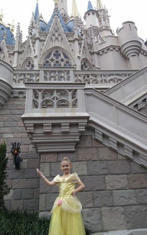 Filha da Manuella vestida de Bela posando atrás do castelo da Cinderela