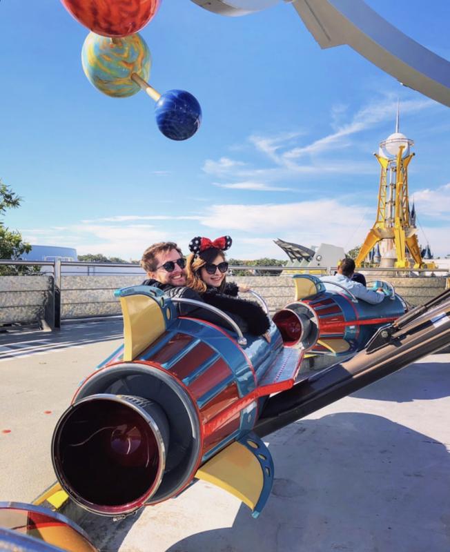 A leitora Bia com o namorado no carrinho do Astro Orbiter, na Tomorrowland, olhando para trás.