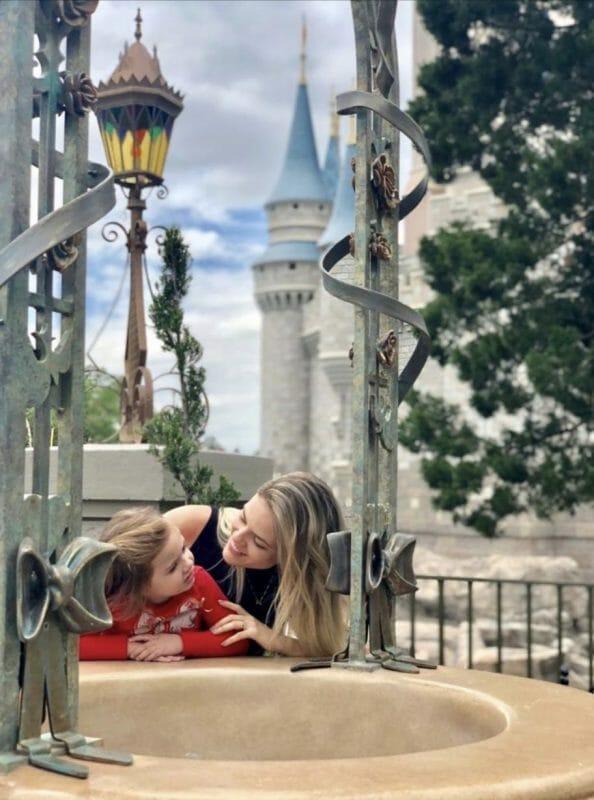 A leitora Flavia com a filha posando na fonte do castelo da Cinderela