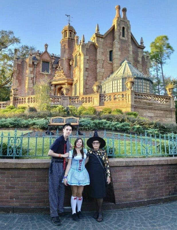 Foto da leitora Aline com a família fantasiados no Halloween, posando em frente à Haunted Mansion