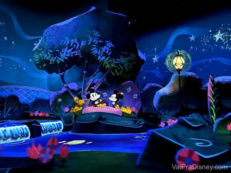 Imagem de divulgação da atração Mickey & Minnie's Runaway Railway, que mostra o Mickey, a Minnie e o Pluto fazendo um piquenique à noite sob árvores.