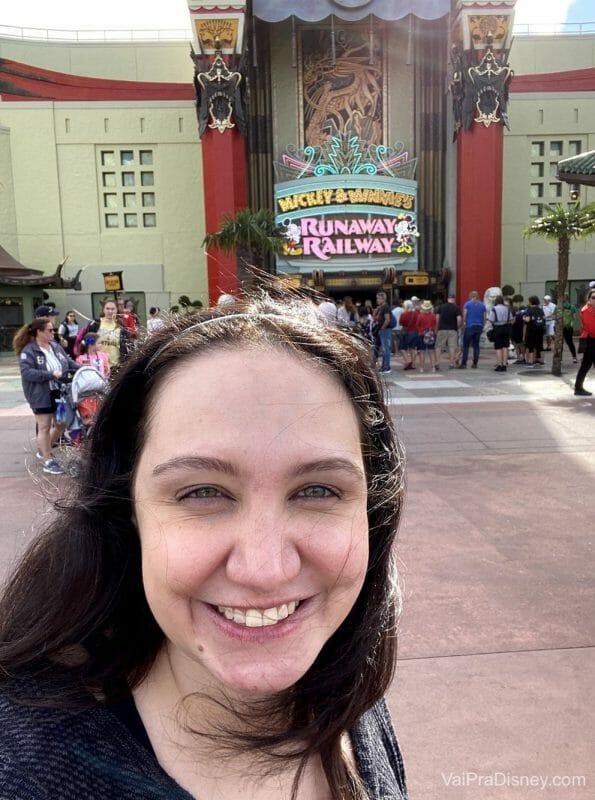 Foto da Renata sorrindo em frente à Mickey & Minnie's Runaway Railway durante o dia, no Hollywood Studios