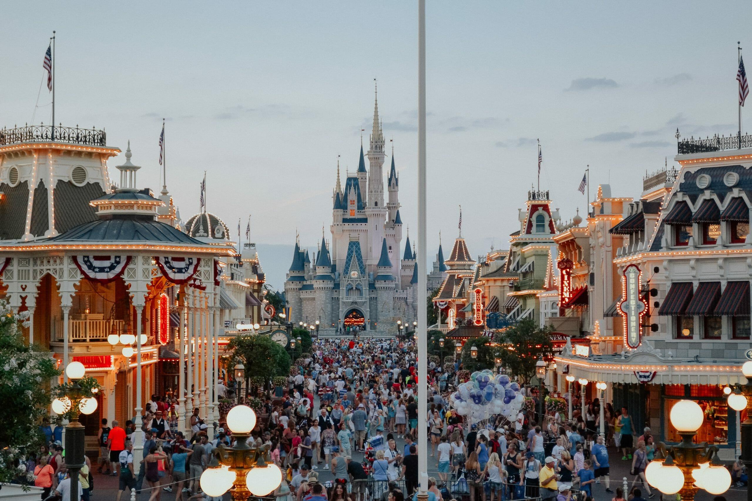 Foto de um dia muito cheio no Magic Kingdom, com o castelo da Cinderela ao fundo e a Main Street começando a ser iluminada.