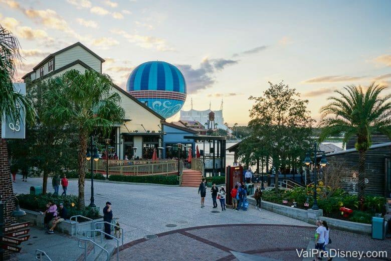 Foto de um fim de tarde em Disney Springs, mostrando o balão da Disney, as árvores e visitantes passeando.