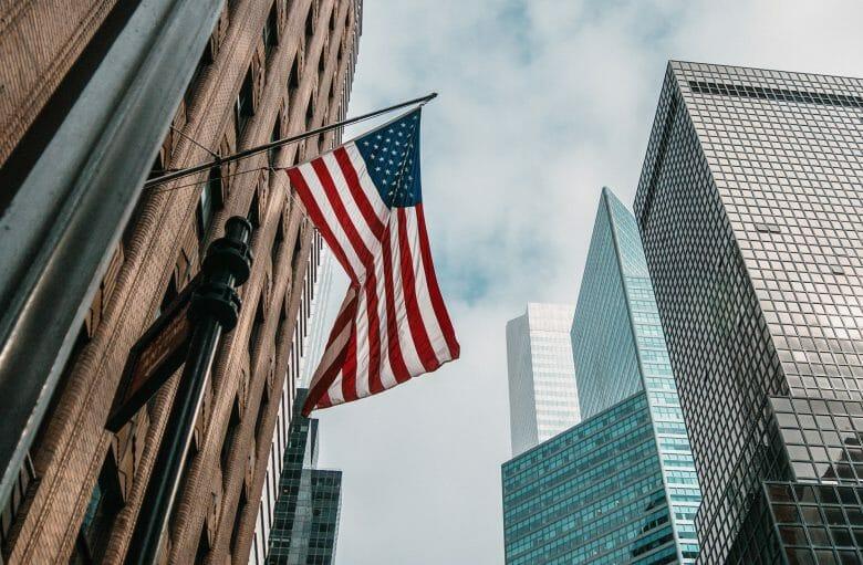 Foto de uma bandeira dos Estados Unidos balançando ao vento, com prédios modernos ao fundo.