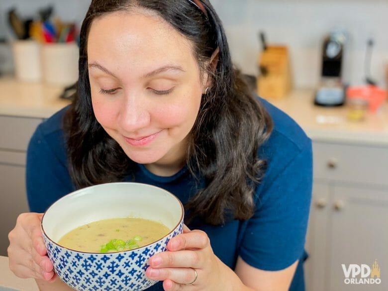 Foto da Renata com uma tigela azul e branca com a sopa de cheddar do Le Cellier, com um pouco de cebolinha picada por cima