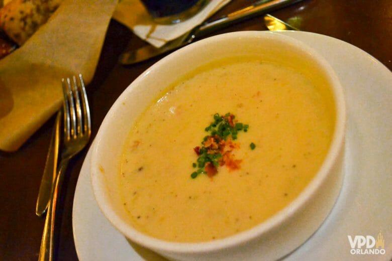 Foto da sopa original do Le Cellier, no Epcot, em uma tigela branca e com temperos verdes e vermelhos sobre ela, no centro.