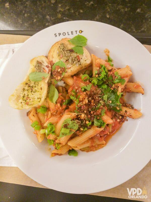 Foto da comida da Carol, que escreveu ao Viagem do Leitor, no Spoleto, um prato com macarrão, molho vermelho, pães com azeite e cebolinha