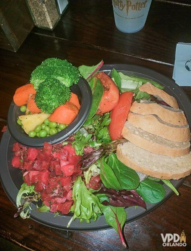 Foto da comida da Carol, que escreveu ao Viagem do Leitor sobre sua experiência como vegana na Disney, um prato com fatias de pão, legumes e folhas