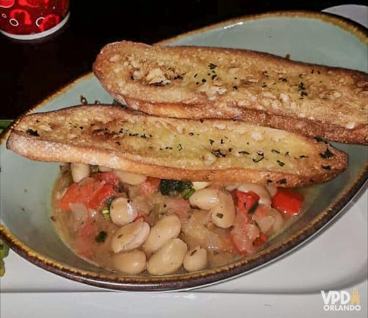 Foto da comida da Carol no Be our Guest, com feijão branco e pães torrados por cima.