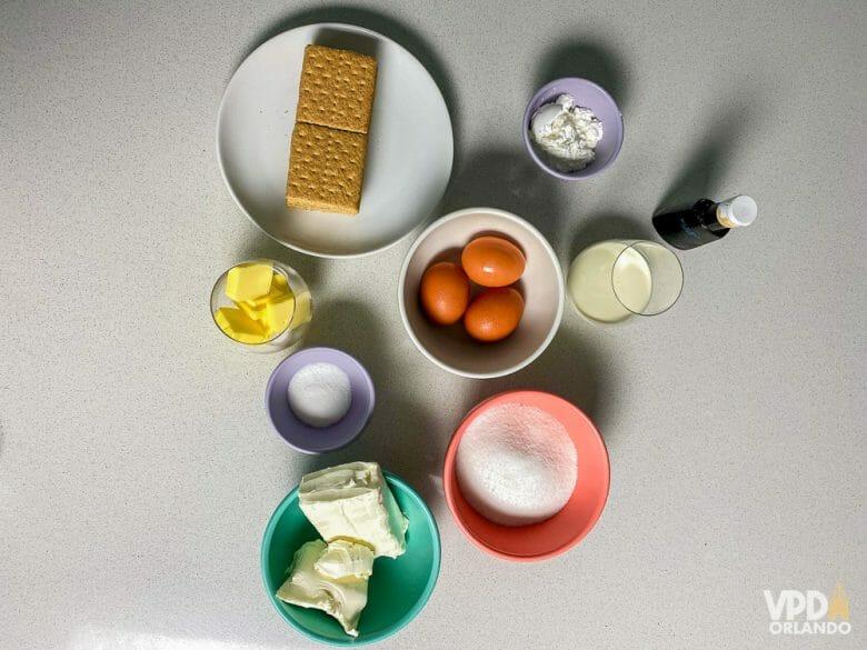 Foto dos ingredientes da receita: bolacha maizena, ovos, manteiga, açúcar, creme de ricota, cream cheese, amido de milho, leite e essência de baunilha.