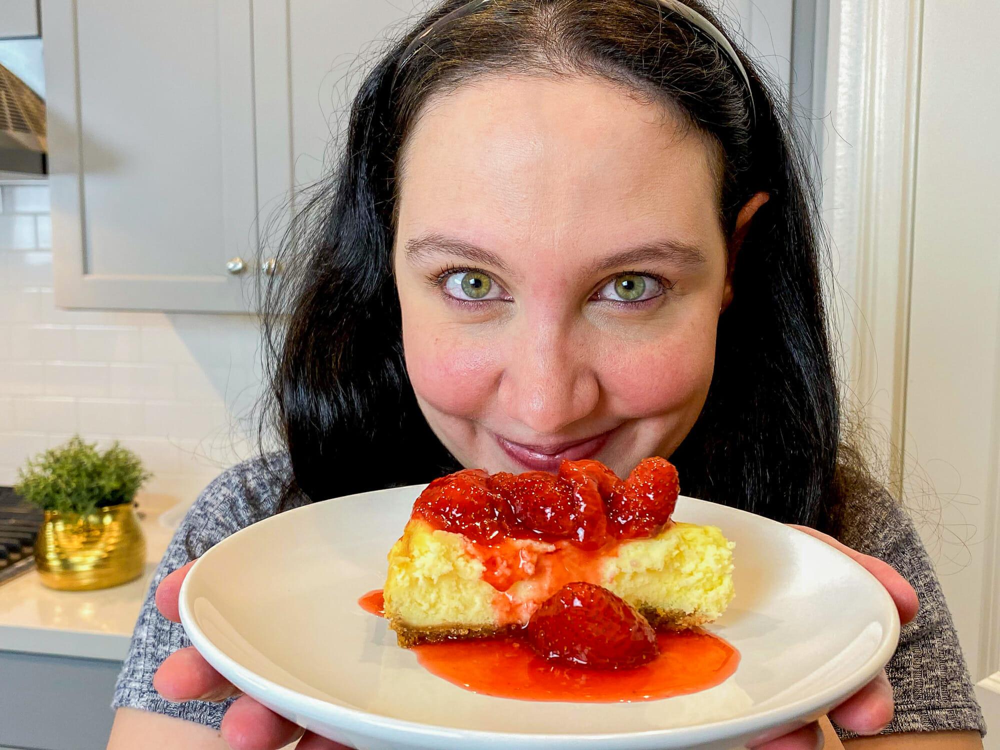 Foto da Renata segurando a fatia de cheesecake da Cheesecake Factory em frente à câmera e sorrindo. A cheesecake está coberta por morangos e calda de morango.