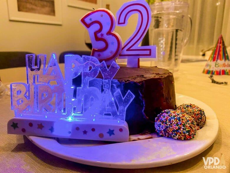 """Foto do bolo de aniversário da Renata, com as velas indicando 32 anos e uma plaquinha iluminada que diz """"Happy Birthday"""", enquanto ela estava em quarentena em Orlando"""