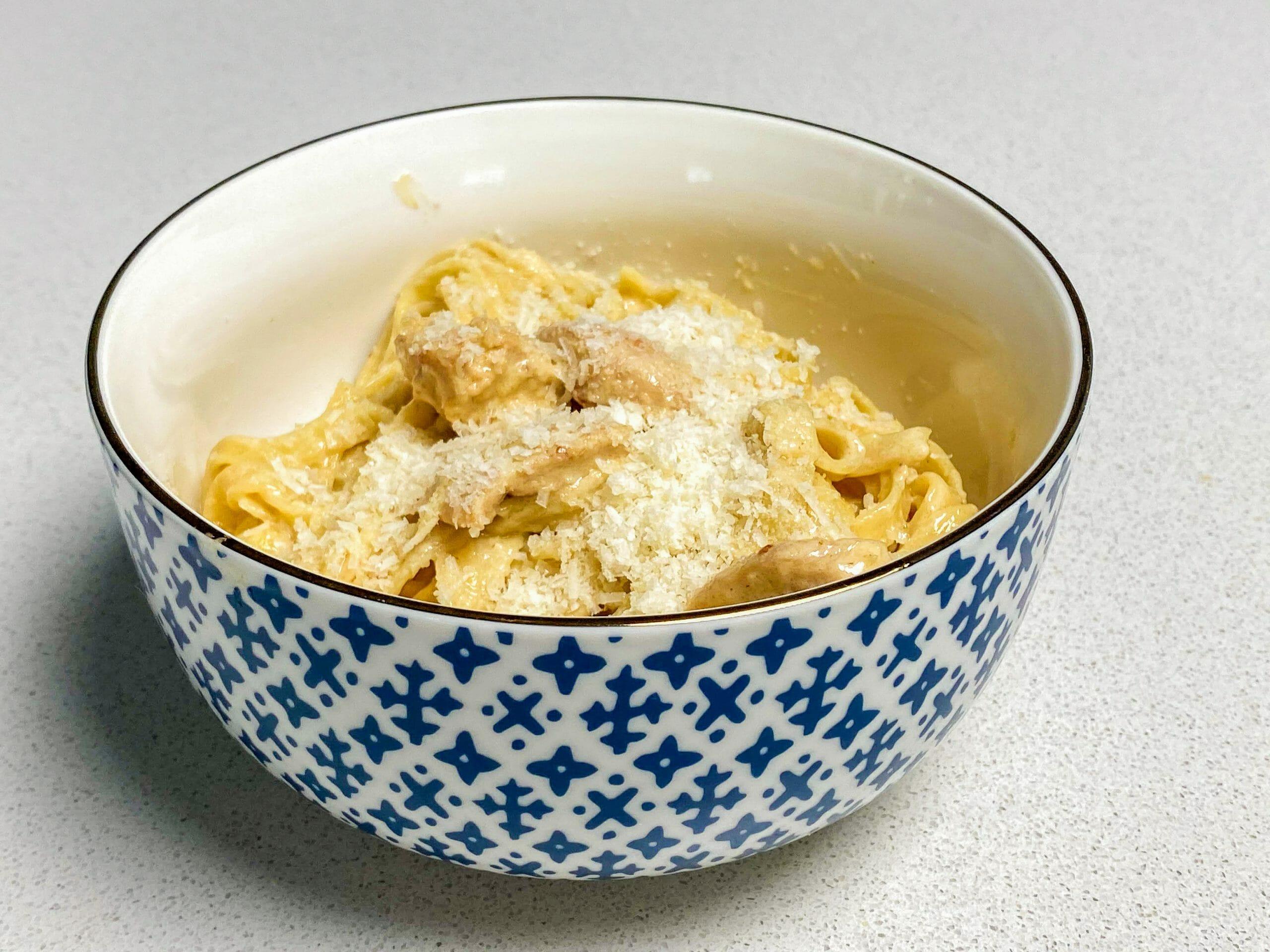 Foto do fettuccine chicken alfredo do Olive Garden pronto, com queijo ralado em cima, em uma tigela azul e branca