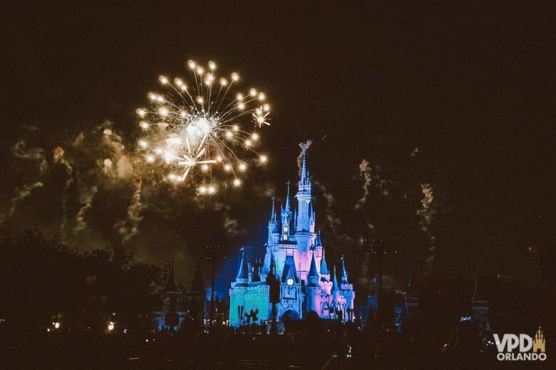 Foto do show de fogos do Magic Kingdom, com o castelo iluminado em azul e rosa, o céu escuro e os fogos estourando.