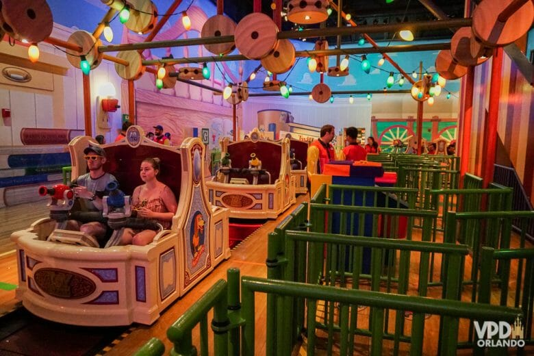 Foto da atração It's a Small World com dois visitantes no primeiro e o carrinho seguinte vazio.