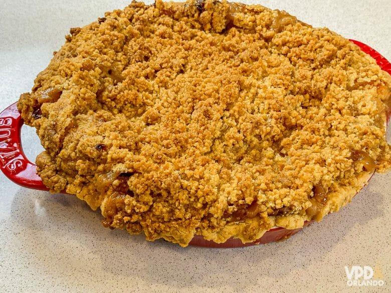 Foto da torta de maçã pronta, em uma vasilha vermelha