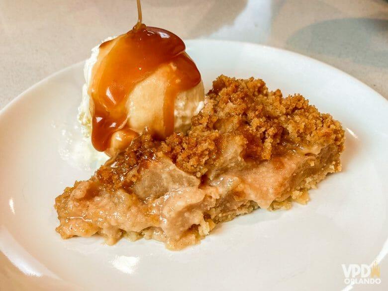 Minha versão da torta do perkins. Foto da fatia de torta de maçã com caramelo em um prato branco, com uma bola de sorvete ao lado coberta por calda de caramelo.
